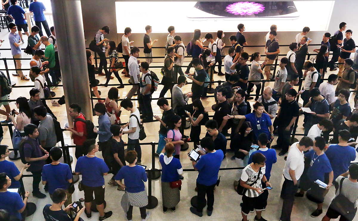Buyers line up outside Apple's flagship IFC store in Hong Kong