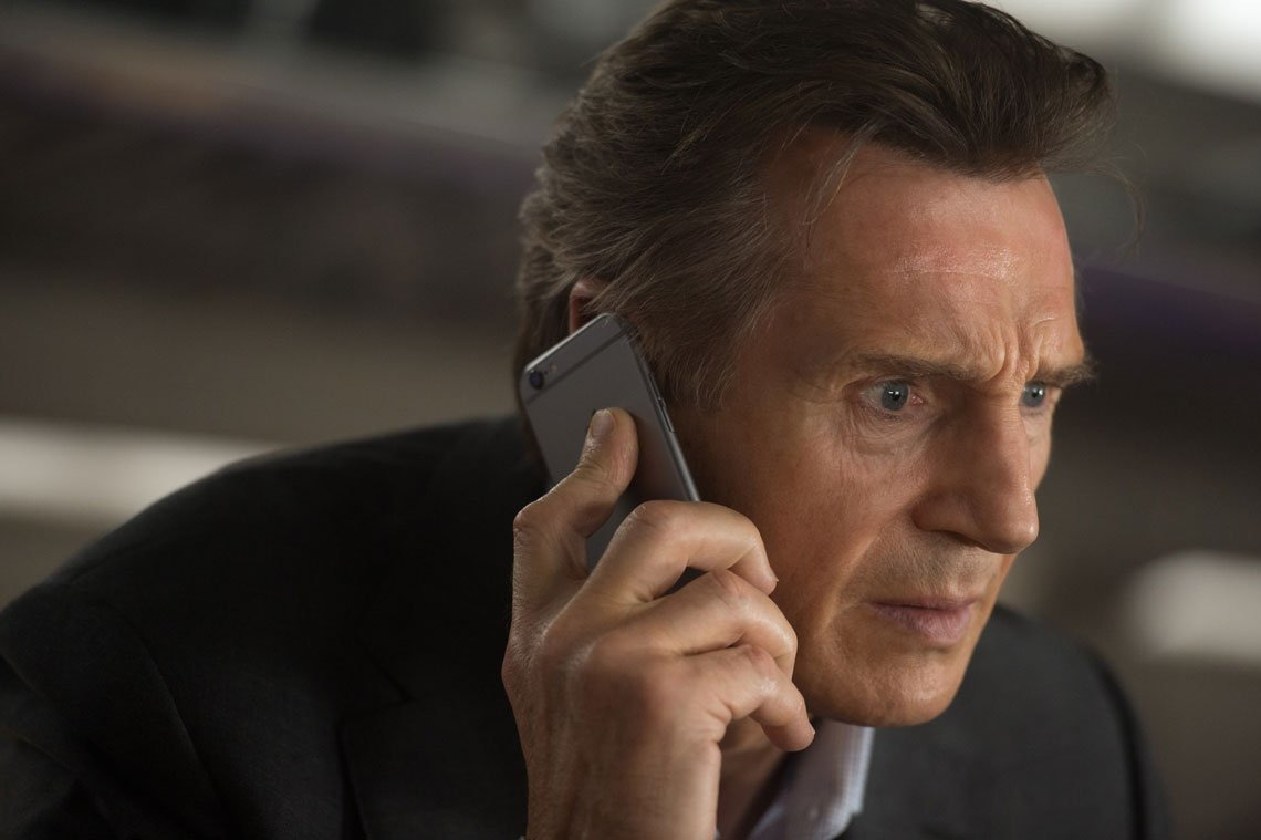Liam Neeson holds an iPhone in The Commuter