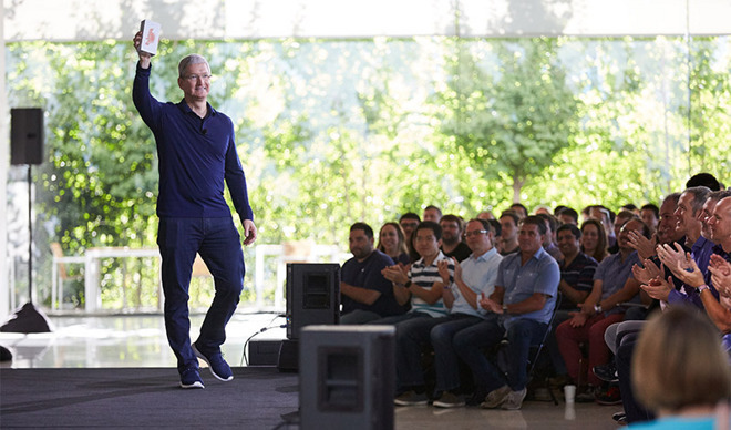 Apple CEO Tim Cook holding an iPhone in front of a crowd