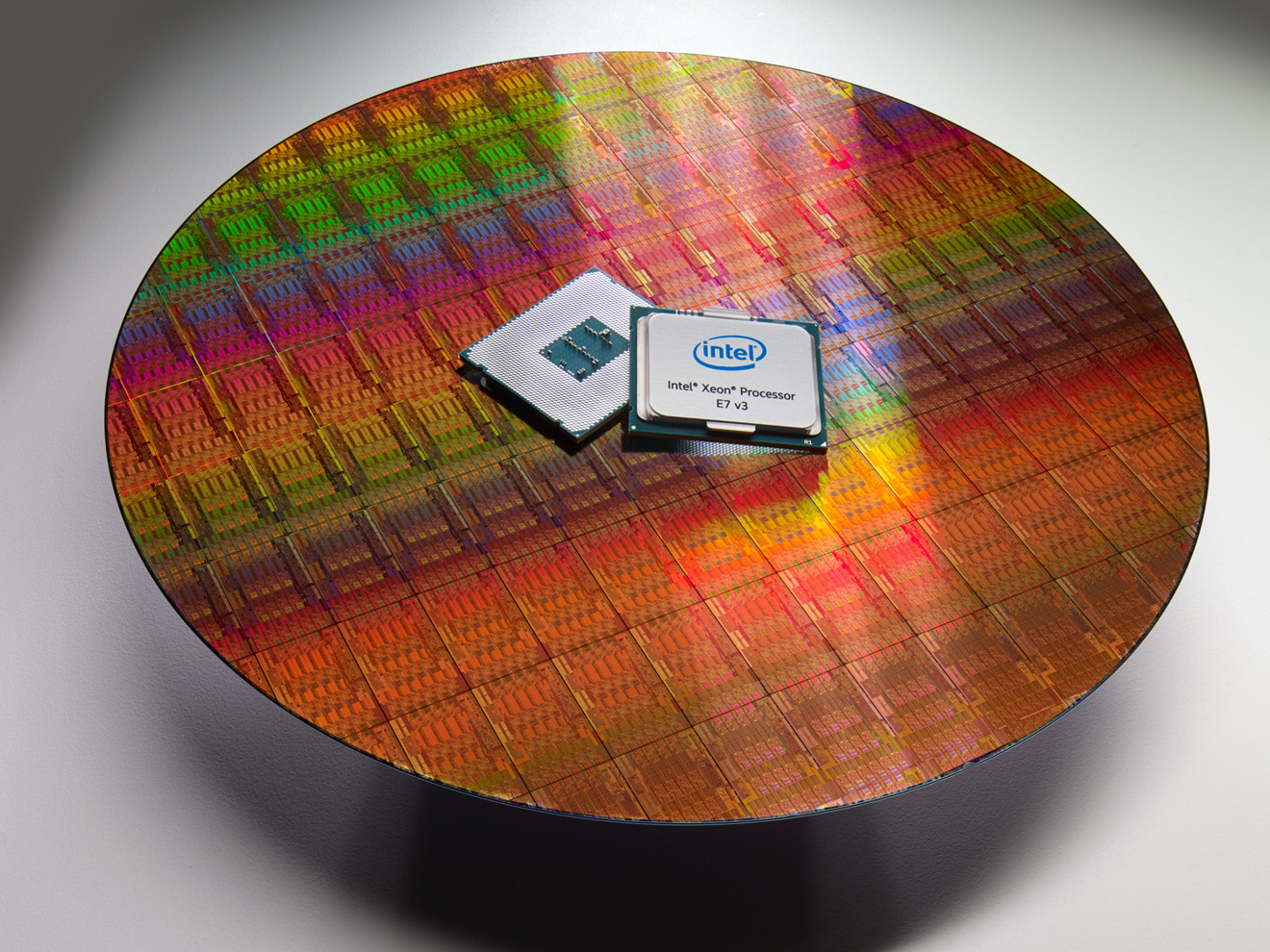 An example of a wafer used to produce Intel's Xeon E7 processor in 2015, with the processor itself for scale.