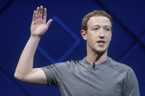 Facebook CEO Mark Zuckerberg puts his hand up for something.