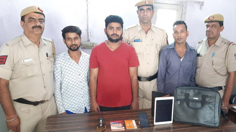 Police officers with three alleged members of the