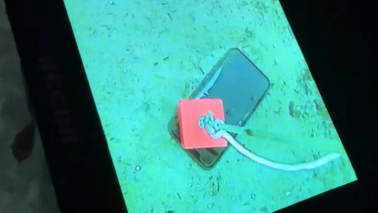 The iPhone seen through a fish finder being pulled up with a strong magnet